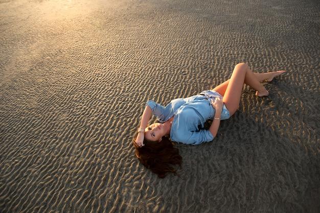 Jong meisje liggend op het zand bij zonsondergang