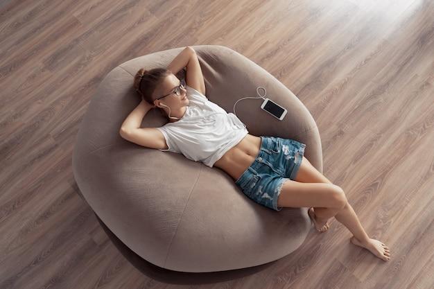 Jong meisje ligt op een stoelzak en luistert thuis naar muziek van je telefoon