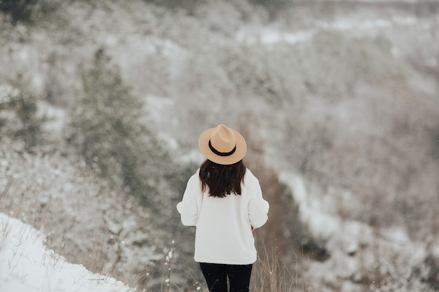 Jong meisje loopt in het winter besneeuwde bos. achteraanzicht.