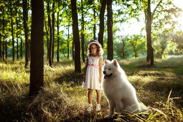 Jong meisje lopen, spelen met hond in park bij zonsondergang.