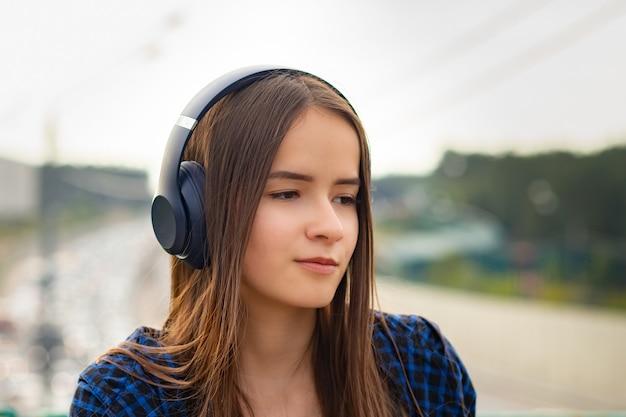 Jong meisje luisteren naar mp3-speler op straat met koptelefoon, smilin