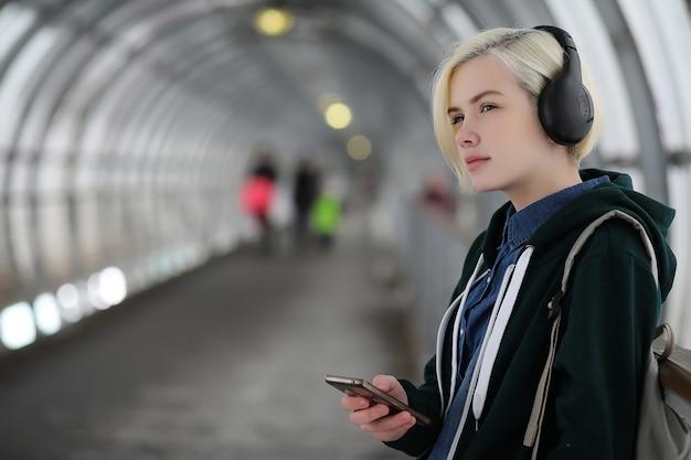 Jong meisje luistert naar muziek in grote koptelefoons in de metrotunnel