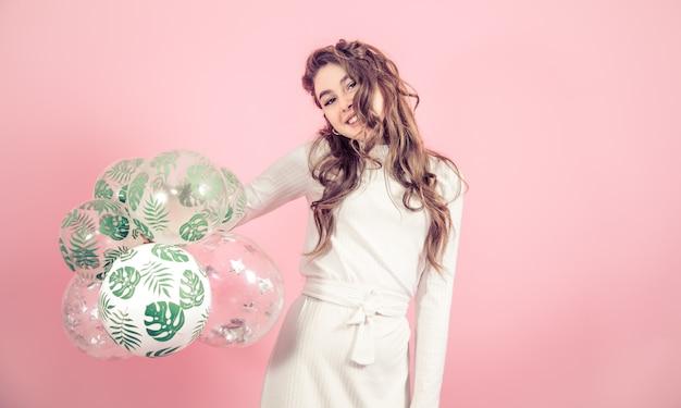 Jong meisje met ballen op een gekleurde achtergrond