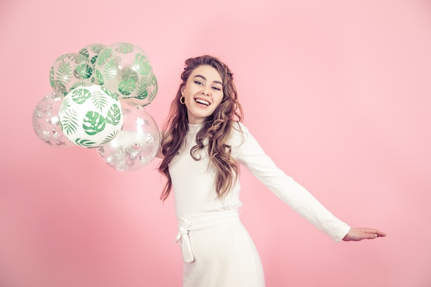 Jong meisje met ballonnen op een gekleurde muur