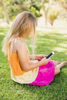 Jong meisje met behulp van de mobiele telefoon