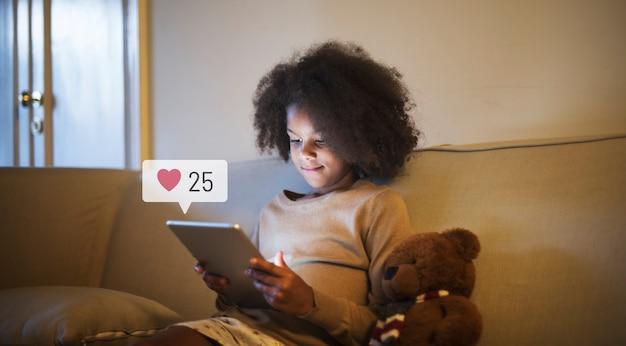 Jong meisje met behulp van een digitale tablet voor het slapen gaan