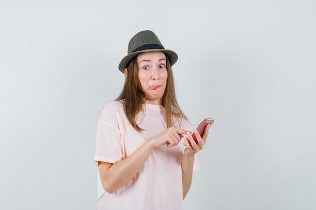 Jong meisje met behulp van mobiele telefoon in roze t-shirt, hoed en nieuwsgierig kijken. vooraanzicht.