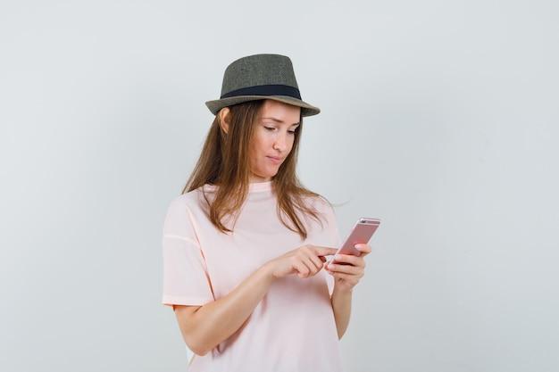 Jong meisje met behulp van mobiele telefoon in roze t-shirt, hoed en op zoek naar drukke, vooraanzicht.
