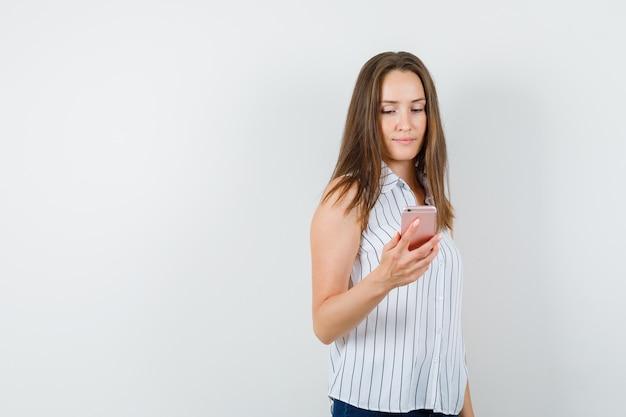 Jong meisje met behulp van mobiele telefoon in t-shirt, jeans en bezig op zoek. vooraanzicht.