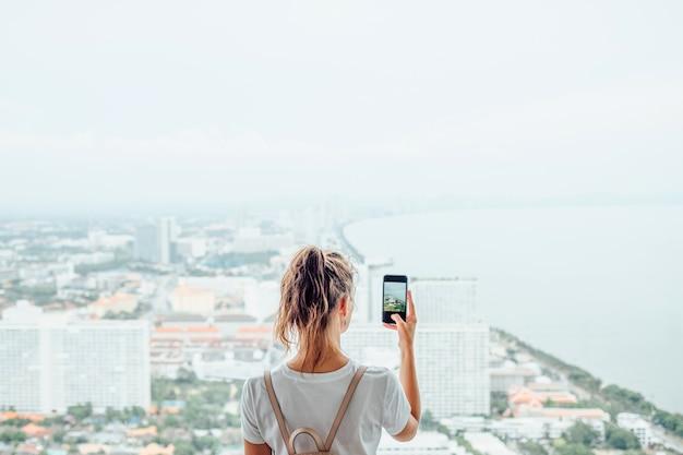Jong meisje met behulp van mobiele telefoon om een foto te maken van de grote stad buiten het raam