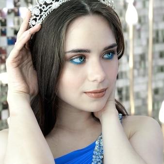 Jong meisje met blauwe ogen die een kroon en een feestelijke blauwe jurk dragen die zich voordeed op de achtergrond van de decoraties van het nieuwjaar.