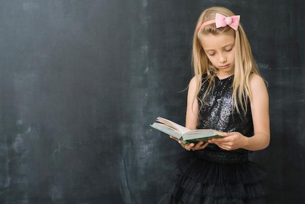Jong meisje met boek op schoolbord