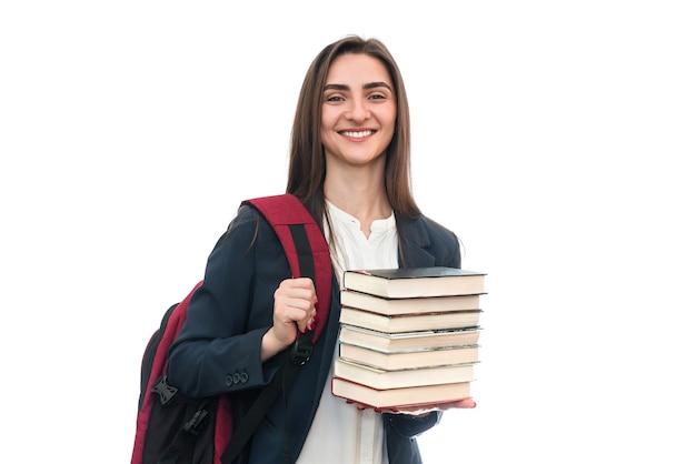 Jong meisje met boeken en tas op wit wordt geïsoleerd