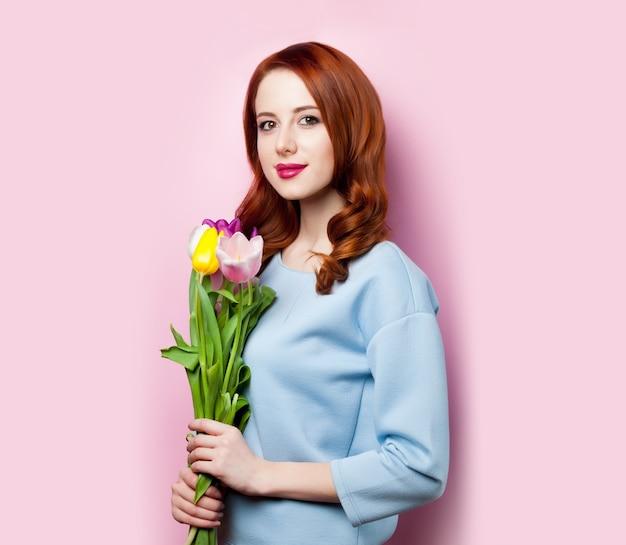 Jong meisje met boeket tulpen op roze