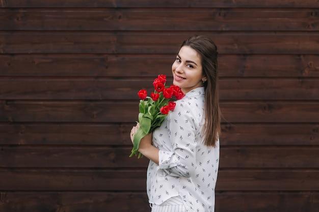 Jong meisje met boeket van rode tulpen staan buiten voor houten achtergrond. gelukkig vrouwtje kreeg een boeket bloemen.