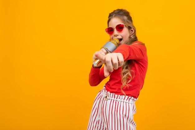 Jong meisje met bril komt uit voor muziek met een microfoon in haar handen op een gele studio achtergrond met kopie ruimte.