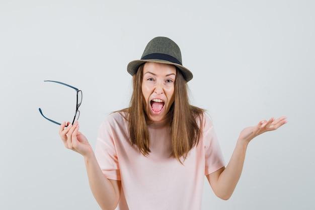 Jong meisje met bril terwijl schreeuwen in roze t-shirt, hoed en op zoek woedend. vooraanzicht.