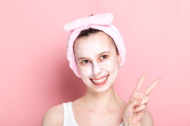 Jong meisje met cosmetische masker op haar gezicht kijkt opzij, glimlacht breed en toont vingers ondertekenen