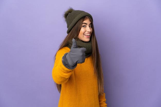 Jong meisje met de winterhoed dat op purpere muur met omhoog duimen wordt geïsoleerd omdat er iets goeds is gebeurd