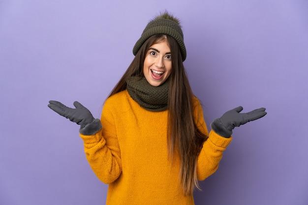 Jong meisje met de winterhoed die op purpere muur met geschokte gezichtsuitdrukking wordt geïsoleerd