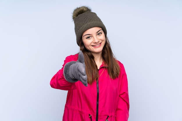 Jong meisje met de winterhoed op blauwe muur het schudden handen voor heel het sluiten