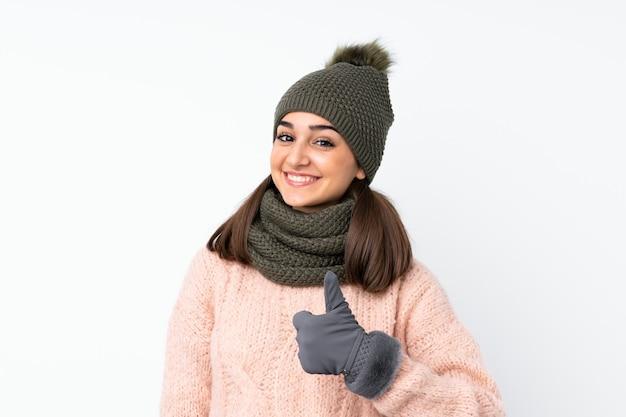Jong meisje met de winterhoed over het geïsoleerde wit geven duimen op gebaar