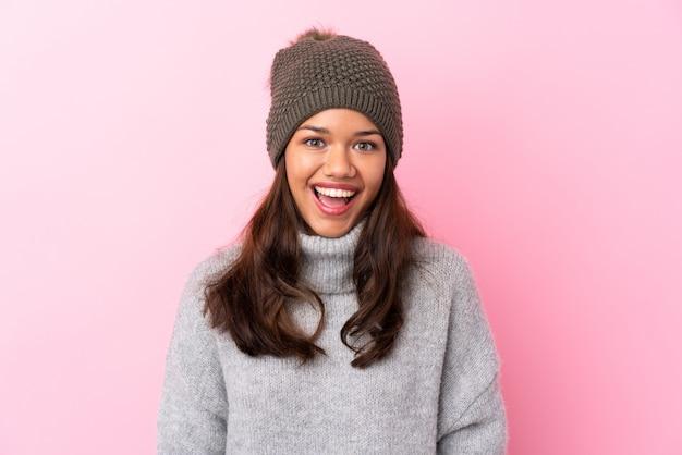 Jong meisje met de winterhoed over roze muur met verrassingsgelaatsuitdrukking