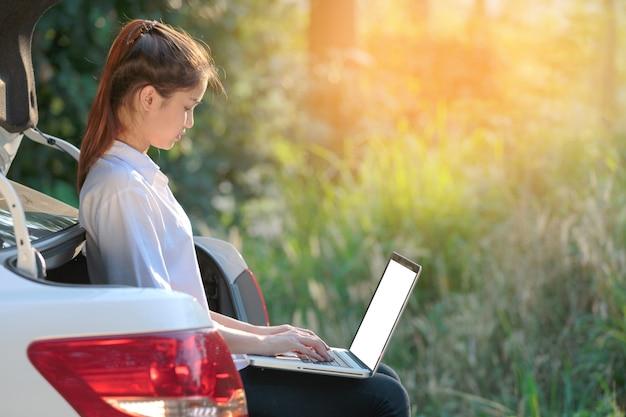 Jong meisje met document en laptop in achterauto.