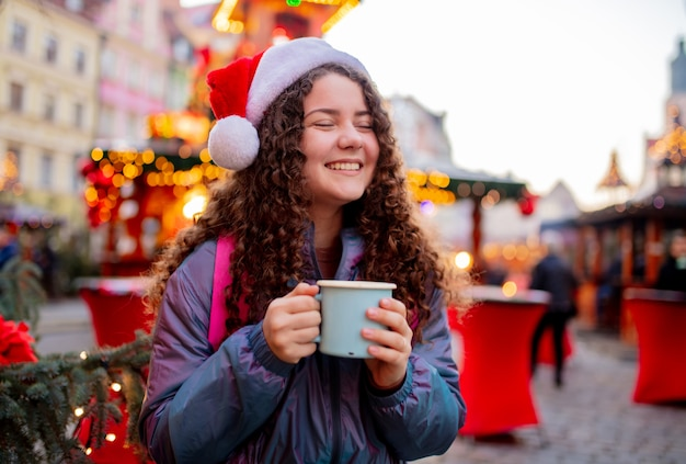 Jong meisje met drankje op kerstmarkt in wroclaw, polen