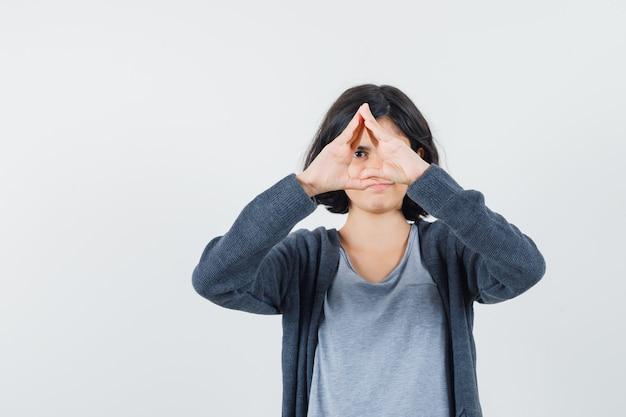 Jong meisje met driehoekige vorm met handen in lichtgrijs t-shirt en donkergrijze hoodie met ritssluiting en ziet er schattig uit,