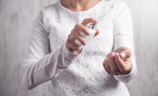 Jong meisje met een fles parfum. parfum aanbrengen