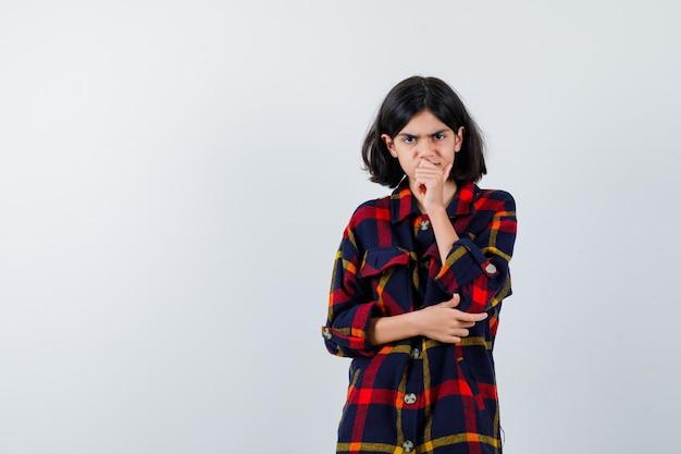 Jong meisje met een hand op de mond. een andere hand op de elleboog in geruit overhemd en gefocust, vooraanzicht.