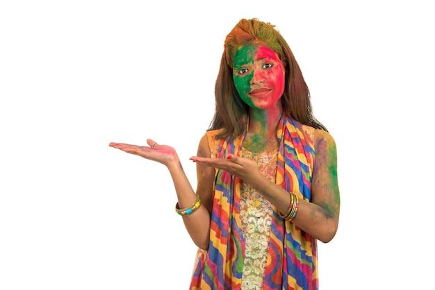Jong meisje met een kleurrijk gezicht dat en iets op de hand houdt voorstelt