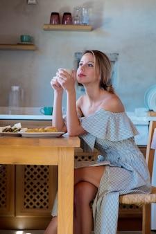 Jong meisje met een kopje koffie of thee op de griekse keuken