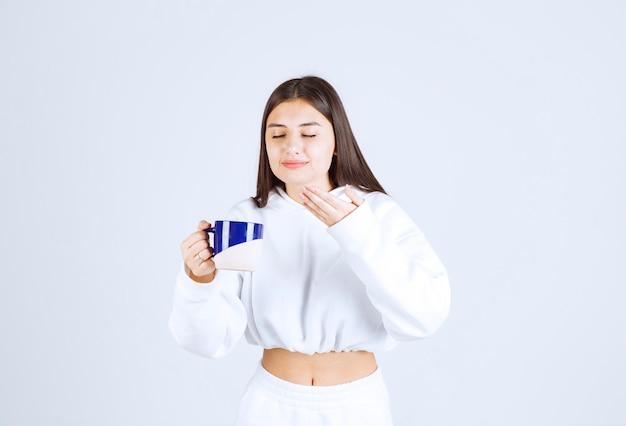 Jong meisje met een kopje op wit-grijze achtergrond.