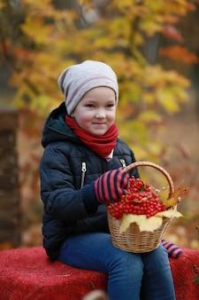Jong meisje met een mand met viburnum in een herfst park