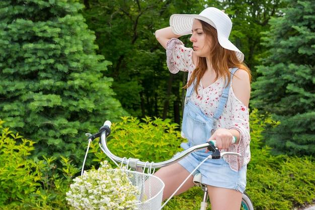 Jong meisje met een mooie witte hoed zittend op haar fiets met een boeket van kleine witte bloemen in een mand in een park met achtergrond van verschillende bomen