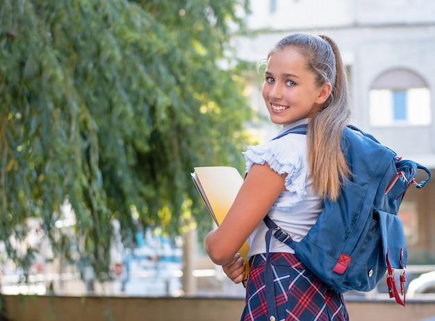Jong meisje met een rugzak en een map lachend