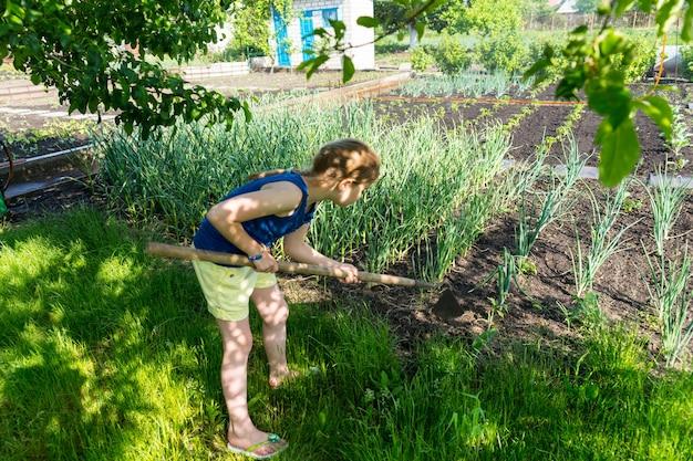 Jong meisje met een schoffel in de tuin wieden tussen de rijen verse jonge groenteplanten in de groentetuin