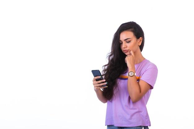 Jong meisje met een videogesprek met een zwarte smartphone en ziet er serieus uit