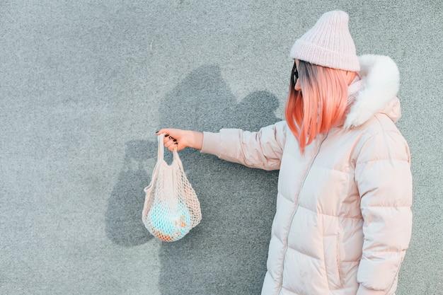 Jong meisje met een wereldbol in een netzak