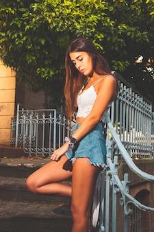 Jong meisje met een wit overhemd en blauwe korte spijkerbroek