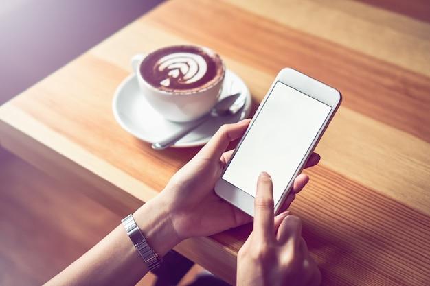 Jong meisje met een witte telefoon heeft een leeg scherm in café
