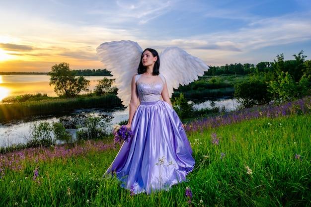 Jong meisje met engelenvleugels zit op een weide met boeket wilde bloemen