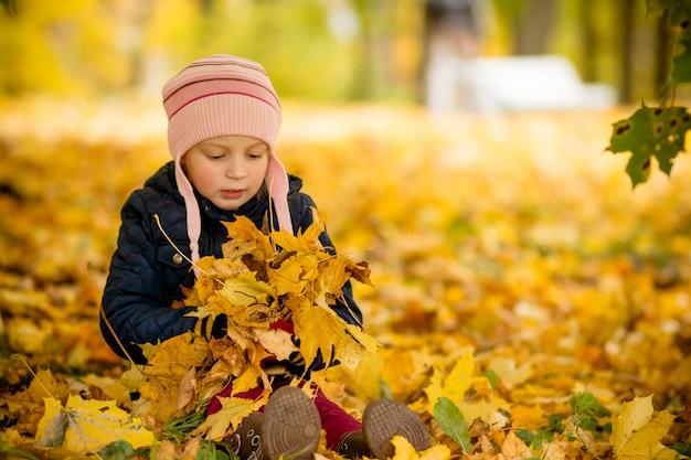 Jong meisje met esdoornbladeren.
