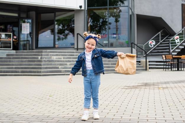 Jong meisje met fast-food tas in de buurt van café buitenshuis