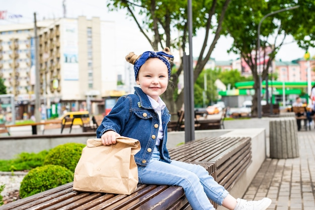 Jong meisje met fast-food tas in de buurt van café zittend op de bank