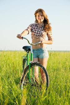 Jong meisje met fiets in gras