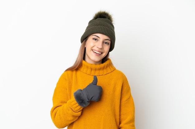Jong meisje met geïsoleerd de winterhoed die een duim omhoog gebaar geeft