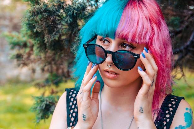 Jong meisje met gekleurd haar in blauw en roze die een zonnebril houdt